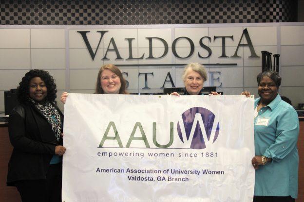Four women holding AAUW banner